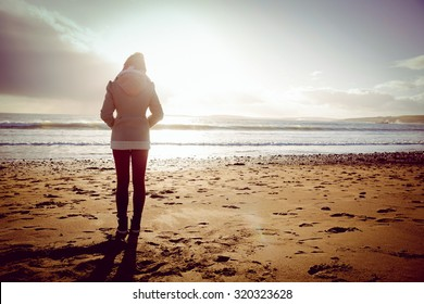 Rear view of woman looking at the sea during the sunset on the beach in front of camera