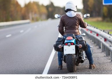 Rear view at woman on a motorcycle resting on the roadside of a country highway with empty road, copyspace