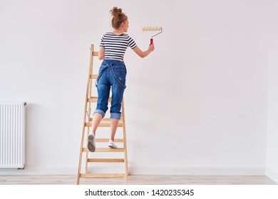 Rear view of woman with paint roller painting wall