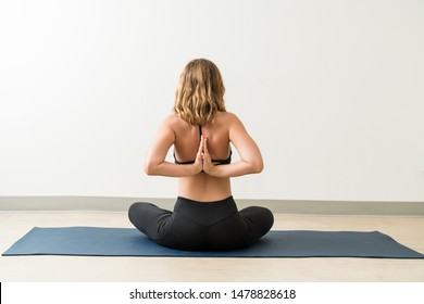 Rear view of woman performing reverse Namaste while sitting on mat during fitness training