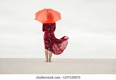Rear view of woman in red dress with umbrella standing at seaside looking at the ocean. Female looking at the sea from the beach.