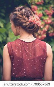 Rear view of woman with red flowers in her updo