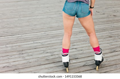 Rear view of a woman roller skater in jeans shorts outdoors