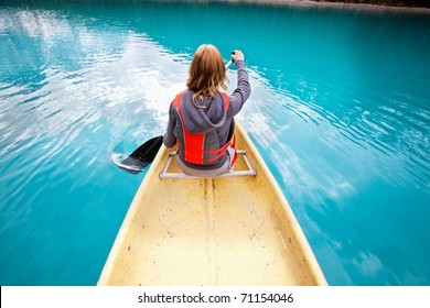 Rear view of woman rowing boat on calm water