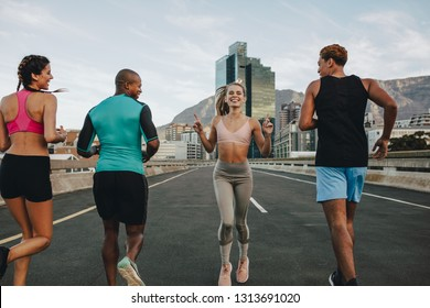 Rear view of woman running backwards with her friends on city street. Group of multi-ethnic friends training together outdoors in morning.