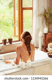 Rear view of a woman sitting in the bath and enjoying water, romantic atmosphere with candles in the bathroom in luxury spa hotel, beauty and health treatment concept