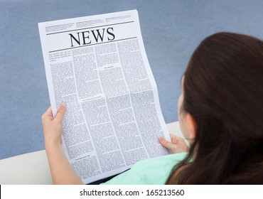Rear View Of A Woman Sitting On Couch Reading Newspaper