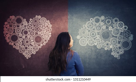 Rear view woman and split blackboard with heart and brain symbol on different sides. Difficult decision, choose between heart and mind. Human character and emotions concept. Introvert and extrovert.
