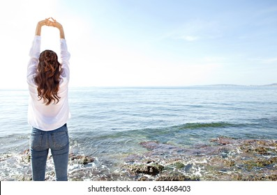 Rear view of woman stretching arms up, breathing fresh air contemplating the blue sea, relaxing in coastal exterior. Healthy well being nature lifestyle, serene morning by the ocean, space background.