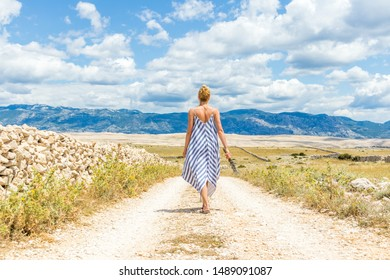 Rear view of woman in summer dress holding bouquet of lavender flowers while walking outdoor through dry rocky Mediterranean coast lanscape on Pag island, Croatia in summertime.
