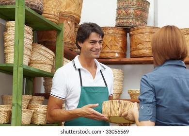 rear view of woman talking with sales clerk in flower shop