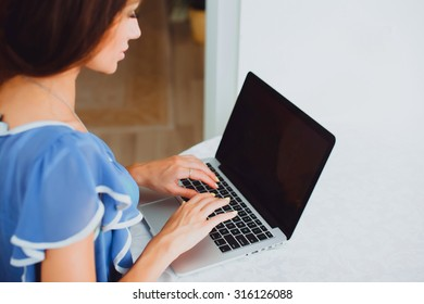 Rear view of woman using laptop on sofa in the living room.young beautiful woman using a laptop computer at home.Close up of a woman hands typing in a laptop in a coffee shop terrace in the street