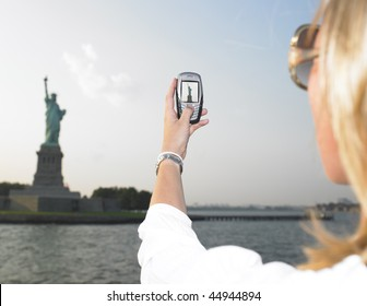 Rear view woman using a mobile phone to take a picture of the Statue of Liberty.  Horizontal shot.