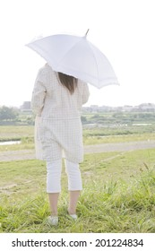 The rear view of the woman walking with a parasol