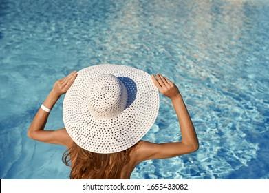 Hintere Ansicht der Frau in weißem Hut sitzend am Pool an einem sonnigen Tag. Seereise-Konzept mit Platz für Ihren Text.