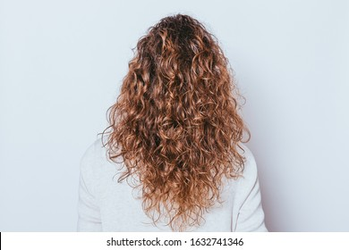 Rear view woman's head with beautiful long naturally curly hair on white background.