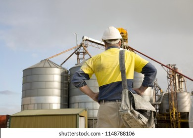 Rear view of a worker standing looking at his work site.
