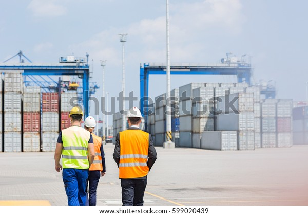Rear view of workers walking in shipping yard
