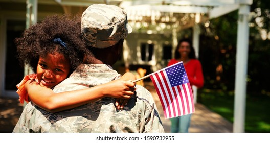 Rear view of a young adult African American male soldier in the garden outside his home, carrying his daughter, who is leaning over his shoulder facing the camera holding a US flag and smiling, her