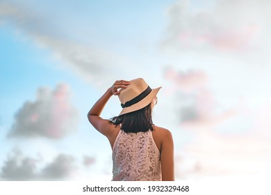 Rear view of young adult asian woman standing relax on the beach sand with sunlight and sky. Wear hat and short hair. Summer travel on holidays concept.