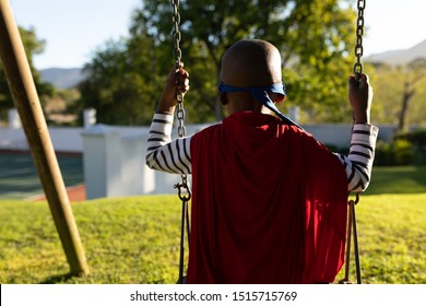 Rear view of a young african american boy dressed in a superhero costume with a red cape and a blue mask in a garden, sitting on a swing