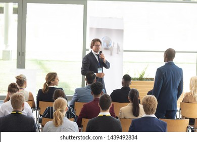 Rear view of young African-american male executive asking question during conference
