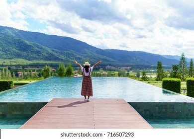 rear view of young asian female standing near the pool and put her hand up for amazing panorama mountain view with blue sky and cloud. travel, tourism, relaxation and happiness concept.