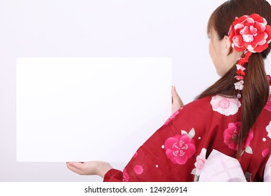 Rear view of young asian woman in traditional clothes of kimono holding a blank board