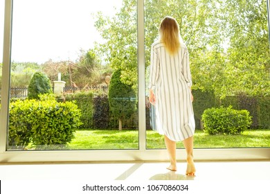 Rear view of young attractive woman standing near big full length window, touching glass. Fit female enjoying garden view on exotic trees, decorative bushes, grass, green lawn. Background, copy space.