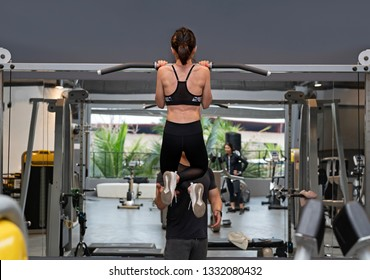 Rear view of a Young attractive woman pulling up on a Chin up bar exercise with trainer in a Gym.