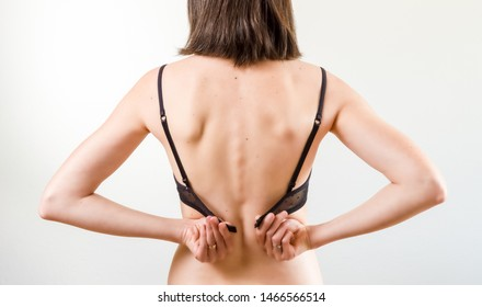 Rear view of young beautiful brunette woman putting on or taking off a black bra with copy space. Daily underwear concept.