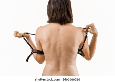Rear view of young beautiful brunette woman taking off a black bra with copy space. Daily underwear concept.