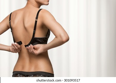 Rear view of young beautiful woman putting on a bra with copy space
