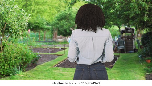 Rear view of young black millennial woman looking around at garden