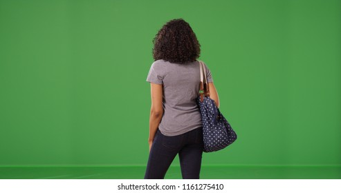 Rear view of young black woman standing holding purse on green screen