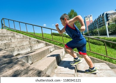 Rear view of young boy running up on steps.