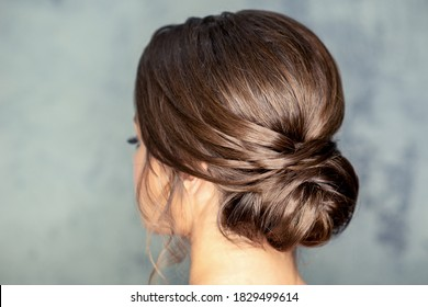 Rear view of young brunette woman with beautiful middle bun hairstyle on gray background