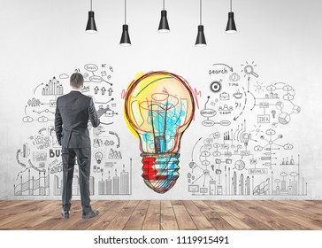 Rear view of a young businessman in a gray suit holding a folder. He is looking forward. A good business idea and a start up mind map on a concrete wall