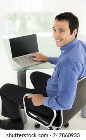 Rear view of a young businessman sitting at workplace and using laptop.