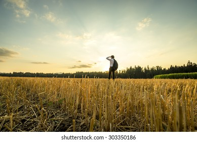 Rear View of a Young Businessman Standing at the Field, Looking Into the Distance During Sunset Time.