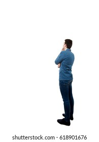 Rear View of a Young  businessman with a thoughtful look full length portrait isolated on white. Project sketch and business planning concept isolated on gray wall background.