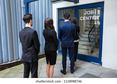 Rear View Of Young Businesspeople Standing At The Entrance Of Job Center