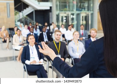 Rear view of young businesswoman doing speech in conference room. With executives in the background.