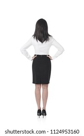 Rear view of a young businesswoman with long black hair standing with her hands on the waist and looking forward. An isolated full length portrait