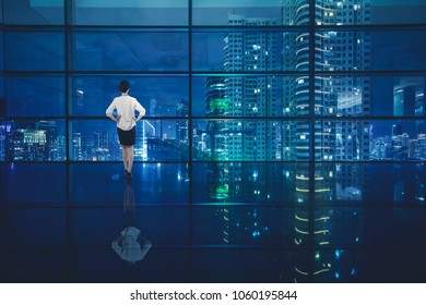 Rear view of young businesswoman standing in the office while looking at a beautiful city through the window at night time