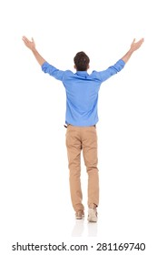 Rear view of a young casual man holding his hand up, celebrating a victory.
