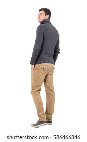 Rear view of young casual man in gray sweater looking up over shoulder. Full body length portrait isolated over white background.