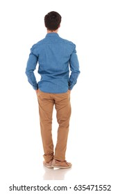 rear view of a young casual man with hands in pockets , full body picture on white background
