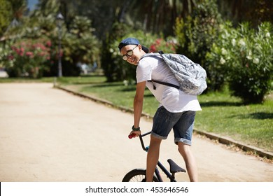 Rear view of young Caucasian BMX rider in street wear and glasses riding his bike, performing tricks, turning his head back, looking and smiling at the camera, cycling against city park background