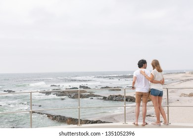 Rear view of young Caucasian couple standing on the promenade at the seaside. They are looking the sea